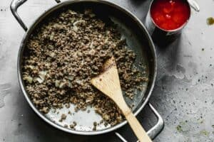 Ground beef cooked with onion in a skillet.