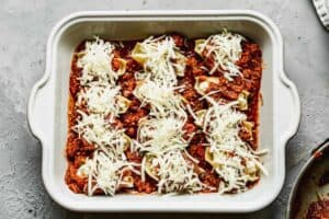 A pan of lasagna stuffed shells with fresh mozzarella on top, ready to go in the oven.