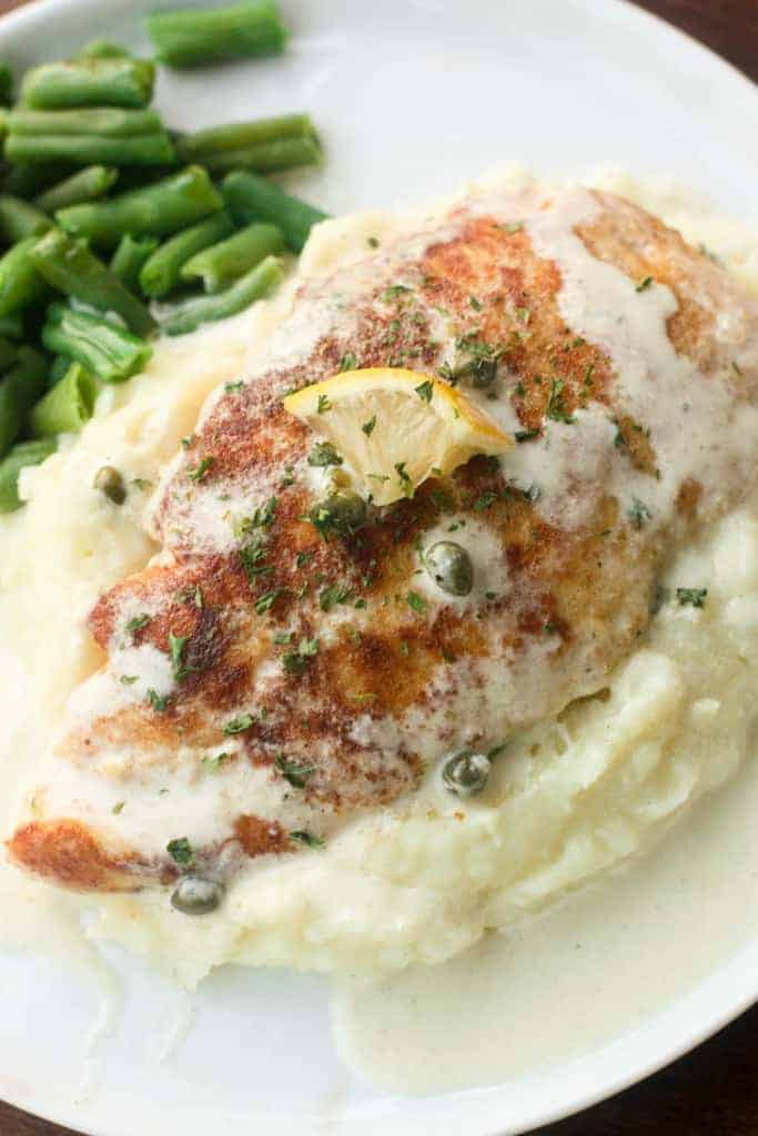 A white circular plate with a heap of mashed potatoes topped with one piece of chicken and smothered in a creamy lemon sauce.