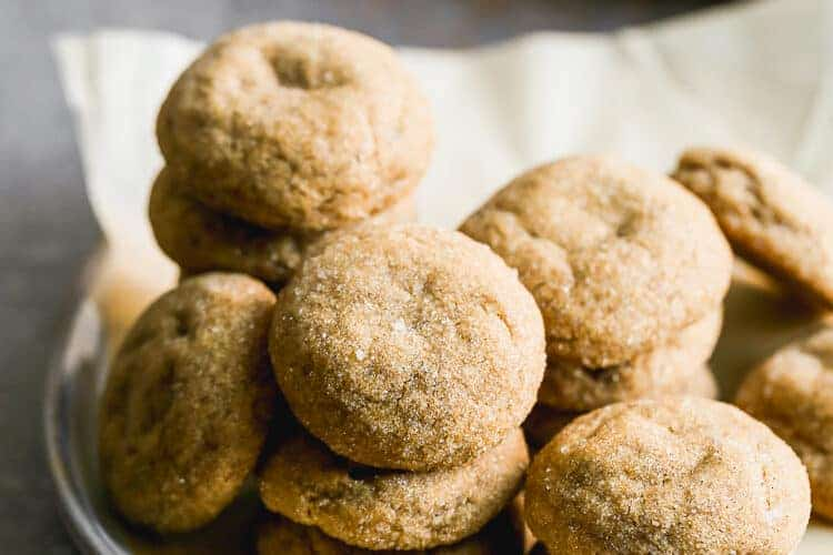 A stack of molasses cookies on a plate lined with parchment paper.