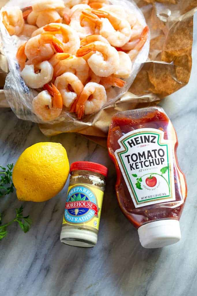 The ingredients to make shrimp cocktail sauce; lemon, horseradish, and ketchup, with fresh cooked shrimp behind.