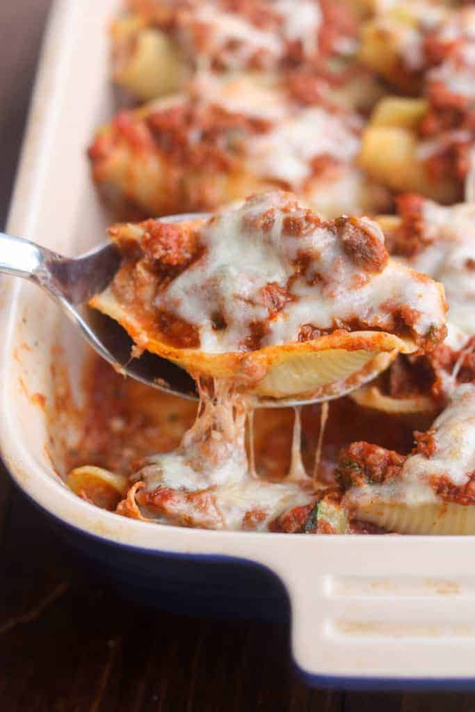 A spoon holding one Lasagna Stuffed Shells with the rest of the lasagna in a casserole dish in the background.