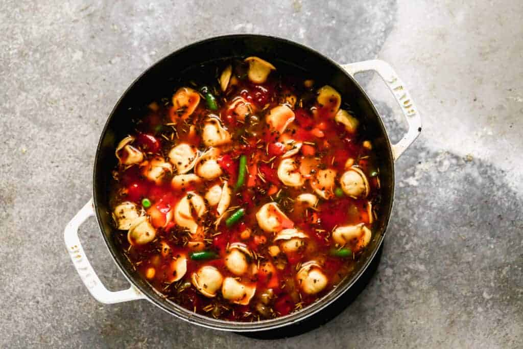 Vegetables and tortellini added to broth in a saucepan to make soup.
