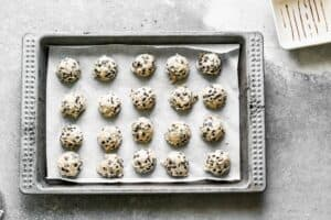 Rolled cookie dough balls on a baking sheet.