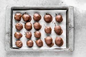 Cookie dough truffles lined on a baking sheet.