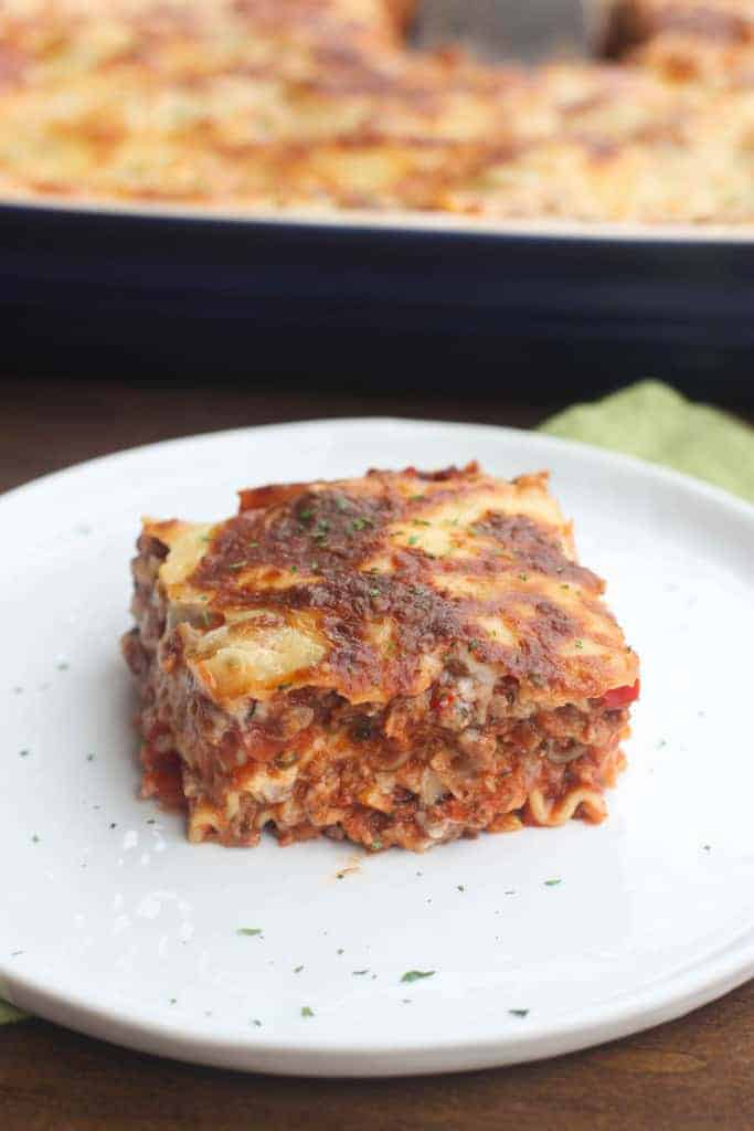 A square slice of Italian Lasagna on a white plate with the rest of the lasagna in a casserole dish in the background.