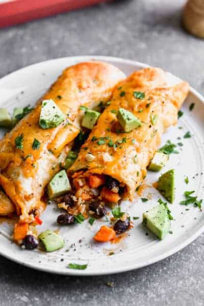 A plate of two vegetarian enchiladas made with sweet potato, black beans and rice.