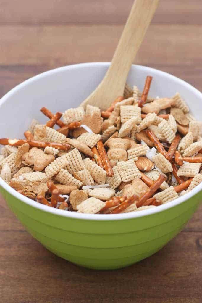 A bowl filled with Chex cereal, Teddy grahams , pretzel sticks, almonds, and coconut with a wooden spoon in it as well.
