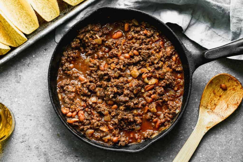 Seasoned taco meat and beans in a skillet, ready to fill shells for baked tacos.