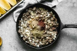 Cooked ground beef and onion in a skillet with taco seasoning spices added on top.