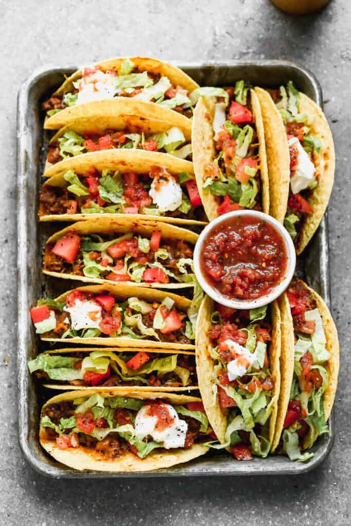 Baked Tacos lined on a baking tray, topped with salsa, sour cream and lettuce.