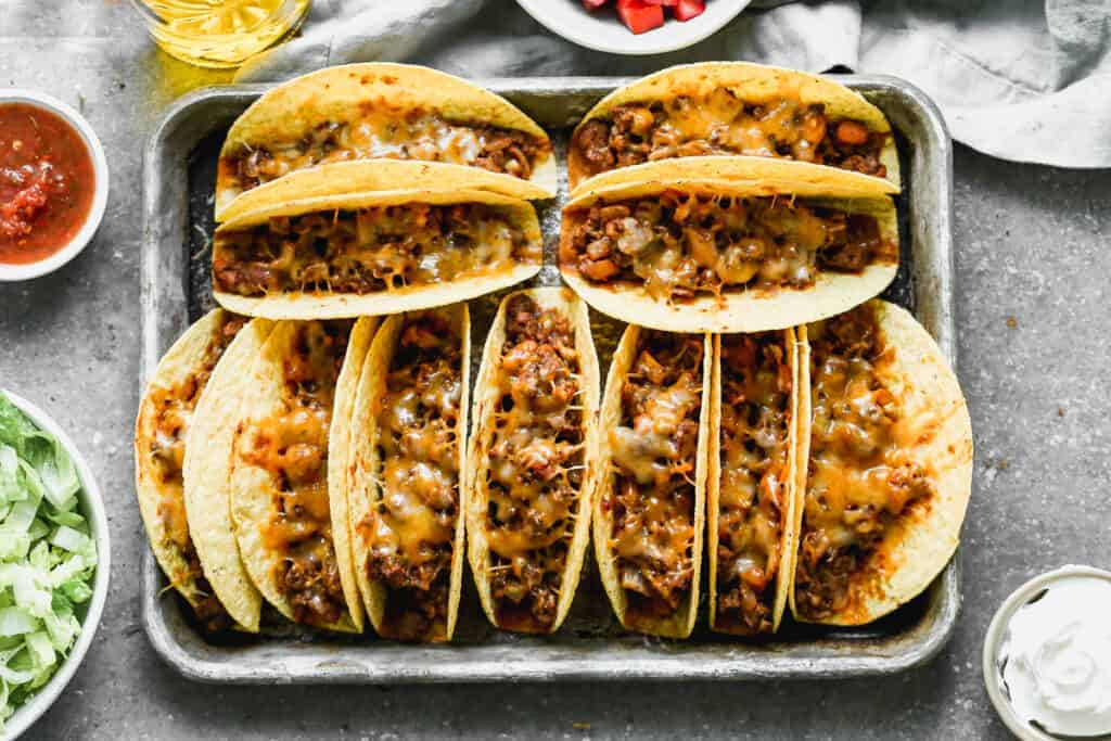 Hard shells tacos filled with a taco meat and bean mixture and topped with cheese, lined on a baking sheet and baked.