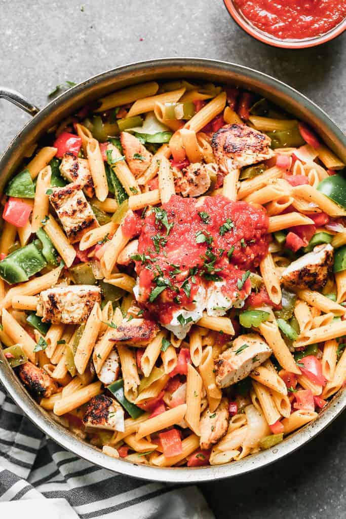 Chicken Fajita Pasta served in a skillet with a scoop of salsa on top.