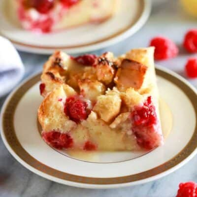 Classic Bread Pudding with raspberries in it and a vanilla cream sauce on top, served on white plate with gold trim and another serving plate in the background.