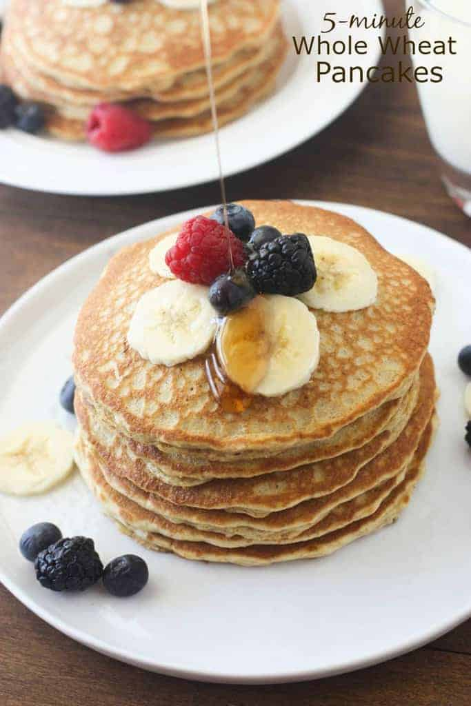 A giant stack of whole wheat pancakes topped with banana slices, blackberries, blueberries, and a raspberry with syrup being drizzled on top.