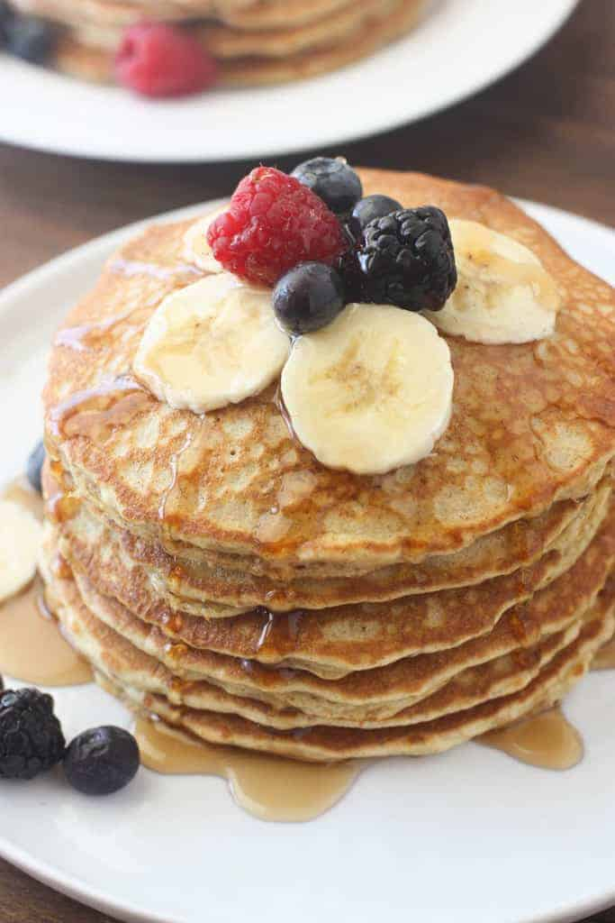 A stack of fluffy whole wheat pancakes topped with syrup and fresh fruit, sitting on a white plate.