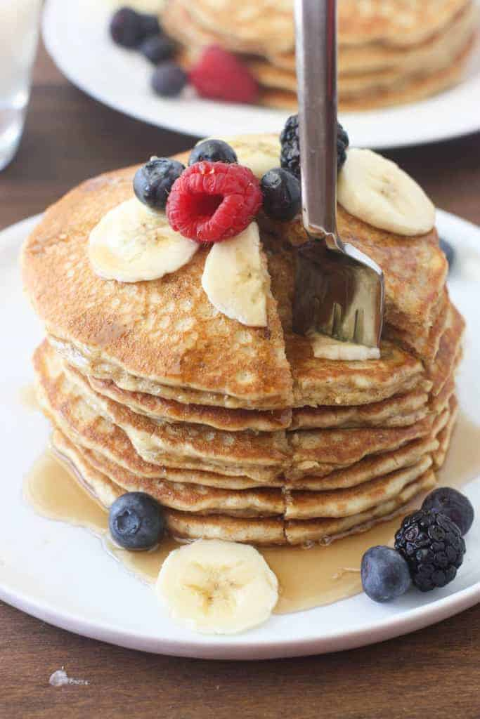 A fork taking a bite out of a stack of whole wheat pancakes with fresh fruit on top.