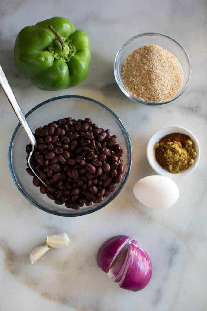 The ingredients needed to make black bean burgers, including black beans in a bowl, green bell pepper, purple onion, egg, garlic cloves, a bowl of spices and a bowl with breadcrumbs.