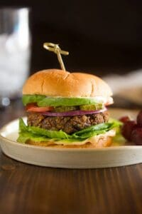 A black bean burger topped with onion, avocado, tomato pickle and lettuce with a toothpick to secure the bun and grapes served on the side.