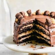 A cake stand displaying a Chocolate peanut butter cake with a few slices removed, showing the layers inside. .