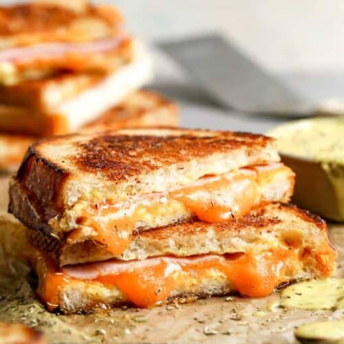 Two halves of a grilled ham and cheese sandwich stacked on top of each other.