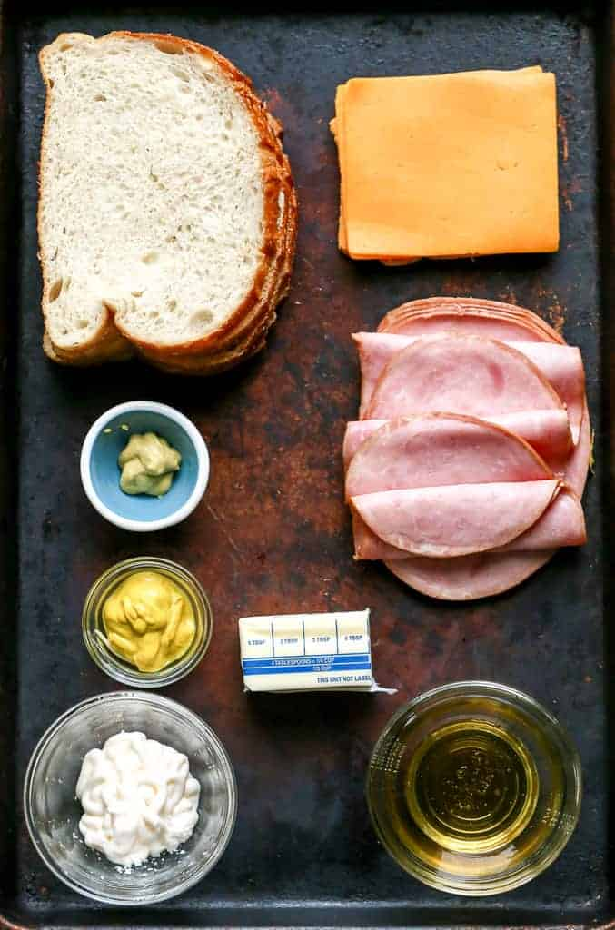 A tray with the ingredients needed to make a grilled ham and cheese sandwich.