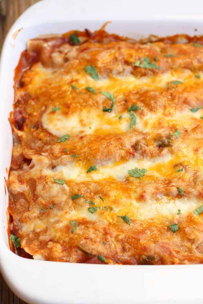 A casserole dish filled with beef enchiladas topped with red sauce and melted cheese.
