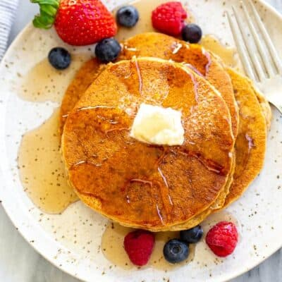 Three whole wheat pancakes on a speckled plate with berries and syrup on top.