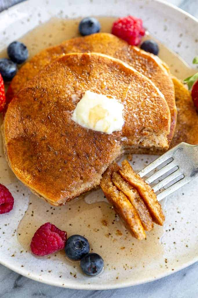 Whole wheat pancakes with a bite on a fork.