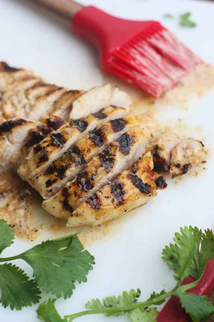 Marinated and grilled chicken on a cutting board.