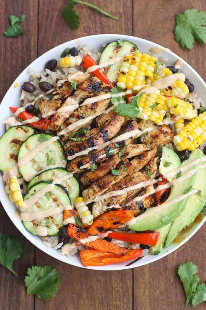 A white bowl filled with chicken and vegetables over black bean rice with bbq ranch dressing.