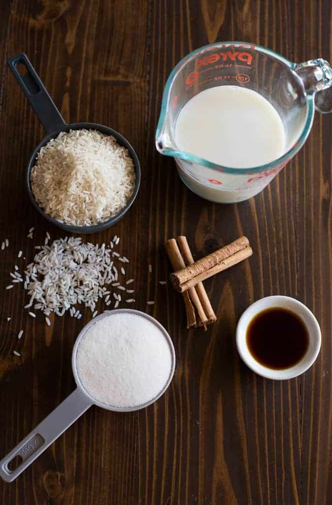 The ingredients for making horchata including a liquid measuring cup with milk, measuring cups with rice and sugar, two cinnamon sticks and a small bowl of vanilla extract.
