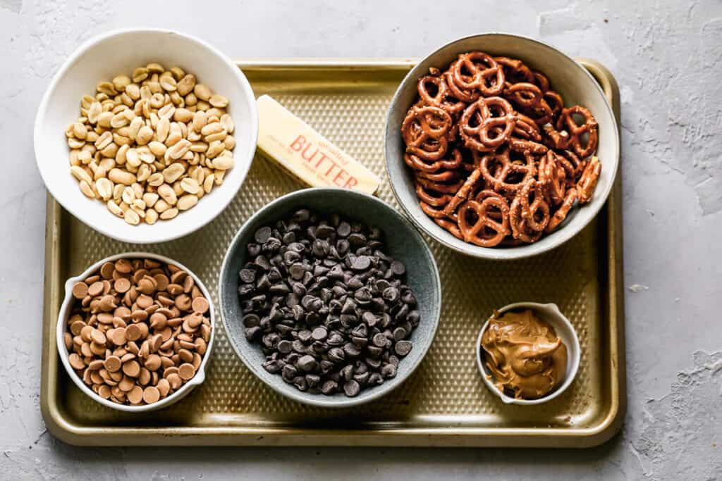 The ingredients needed to make peanut clusters, including peanuts, chocolate, peanut butter chips, peanut butter, butter and pretzels.
