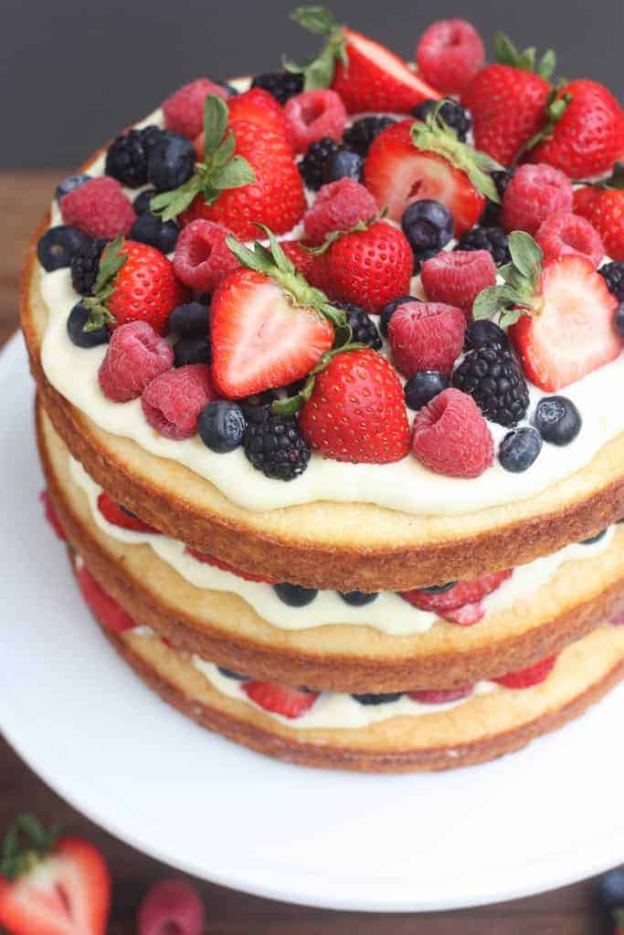 A three layer cake topped with lemon mousse and assorted berries.