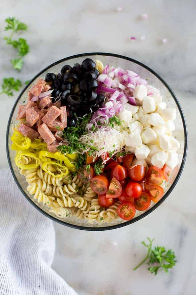 Overhead photo of the ingredients for Italian pasta salad, in a bowl, including cooked pasta, cherry tomatoes, olives, cheese, onions and salami.