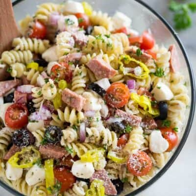 Cold Italian pasta salad with rotini noodles, mozzarella, tomatoes, olives, and salami in a clear glass bowl.