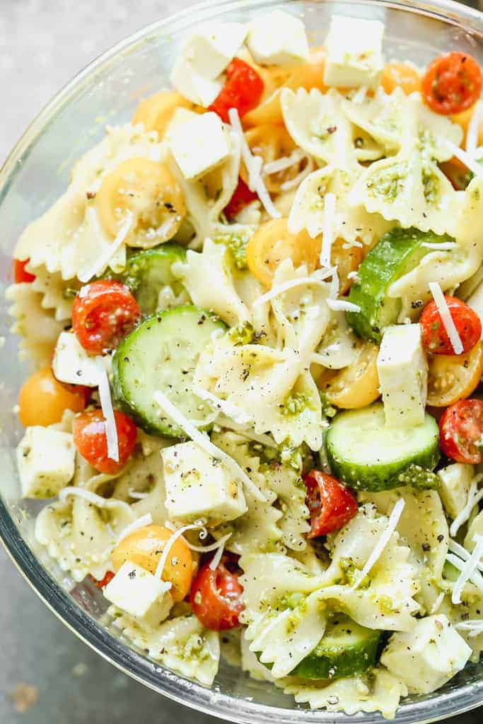 A mixing bowl with the ingredients for pesto pasta salad tossed together.