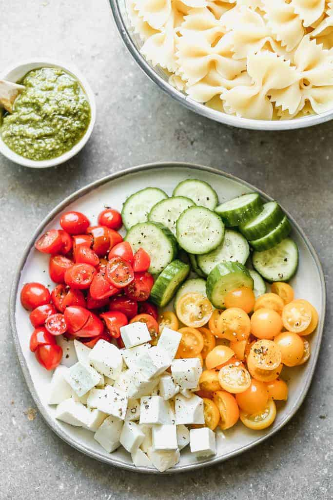 The individual ingredients needed to make pesto pasta salad.