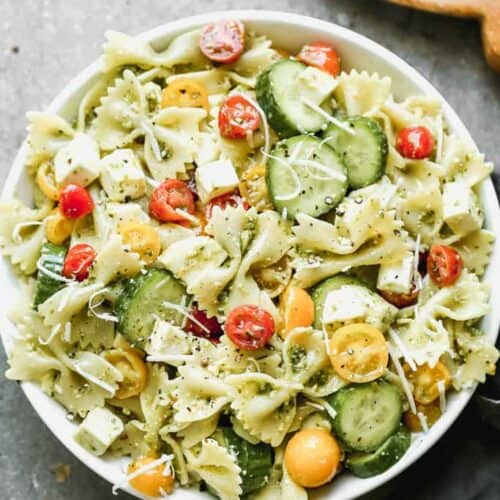 A bowl full of pesto pasta salad with farfalle noodles, red and yellow cherry tomatoes, mozzarella, cucumbers, tossed in pesto sauce.