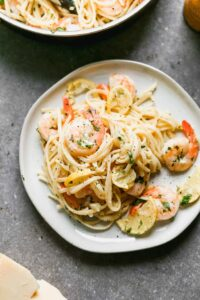 Shrimp scampi served over pasta, on a plate.