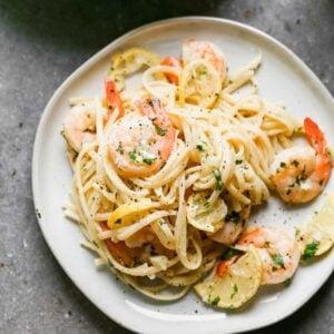 Shrimp scampi served over pasta, on a plate.