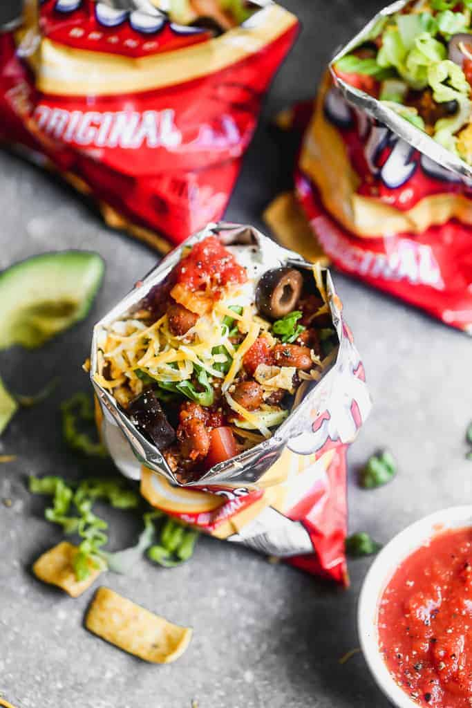 A Walking taco, bag of fritos chips layered with taco toppings.