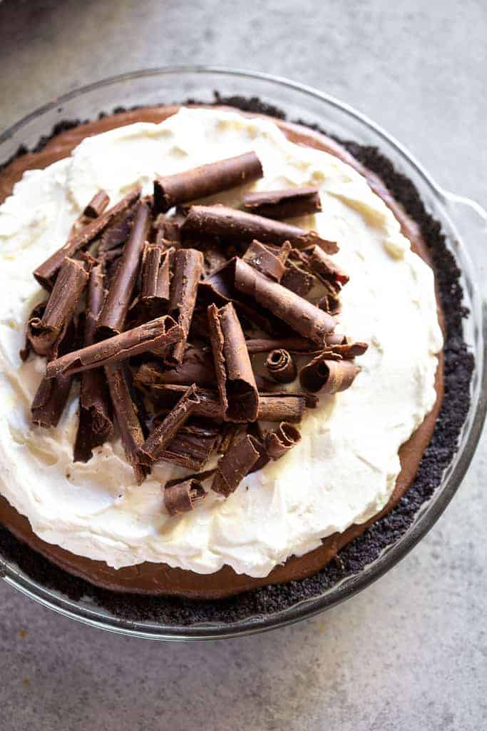 Chocolate cream pie with an oreo crust, baked in a clear pie dish, with whipped cream and chocolate curls on top.