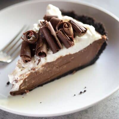 A slice of chocolate cream pie with whipped cream and chocolate curls on top, on a white plate with a fork.
