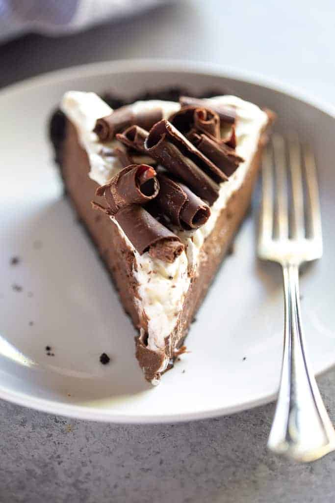 A front view of a slice of chocolate cream pie with whipped cream and chocolate curls on top.