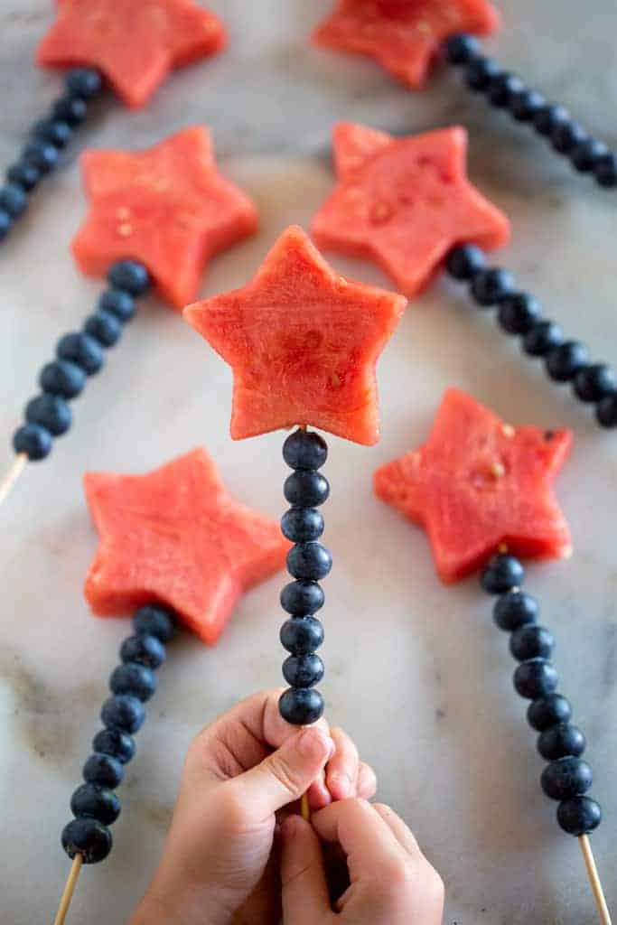 Two hands holding a wooden skewer lined with blueberries and a watermelon cut into the shape of a star, on the top.