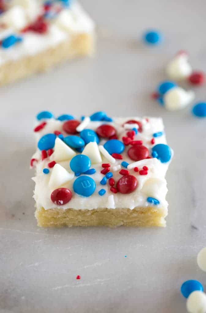 A patriotic sugar cookie bar with white frosting and red, white and blue sprinkles and candy on top.