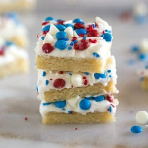 Three stacked, frosted sugar cookie bars decorated with red, white and blue sprinkles and candy on top.