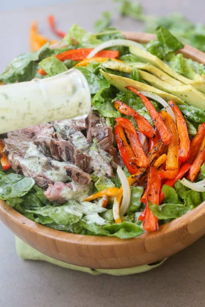 Steak Fajita Salad with Cilantro Lime Dressing. Marinated and grilled flank steak served over a large salad with grilled onions and peppers. This Steak Fajita Salad with Cilantro Lime Dressing is better than anything you'd find at a restaurant! It's also great with leftover steak. | Tastes Better From Scratch