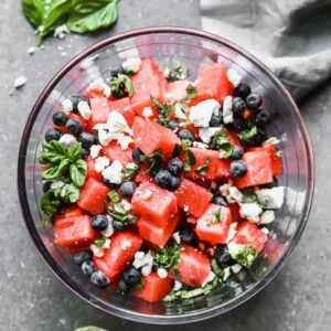 A bowl of watermelon salad with feta, blueberries and fresh basil in it.